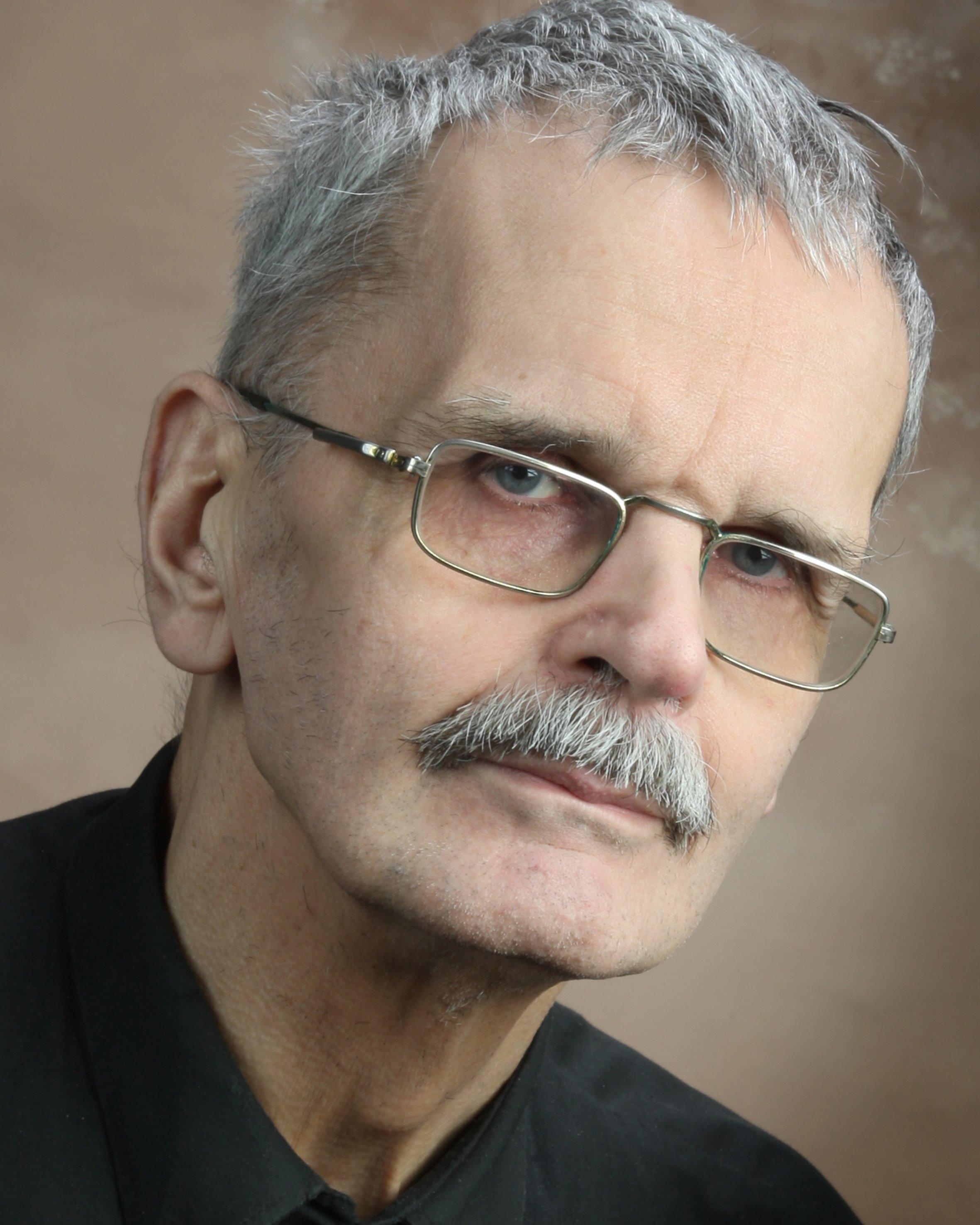 Porträtt av Gösta Ågren, en man med grått hår, mustasch och glasögon